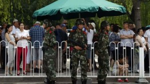 Paramilitary soldiers stand guard in front of visitors in a queue to undergo security checks before entering Tiananmen Square in Beijing